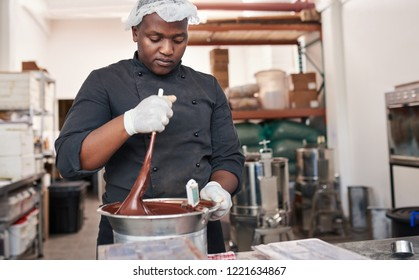 Worker standing at a table in an artisanal chocolate making factory mixing melted chocolate in a bain marie with a spoon
