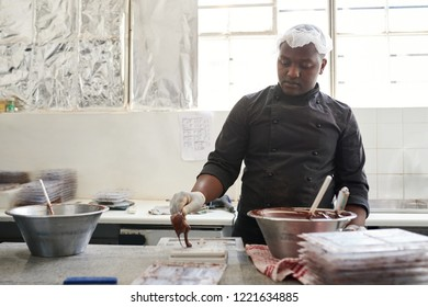 Worker standing at a table in an artisanal chocolate making factory pouring melted chocolate into molds