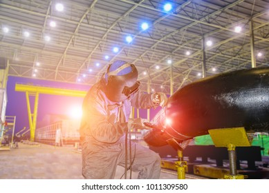 worker standing welding steel with protective mask in factory on constructio and twilight background