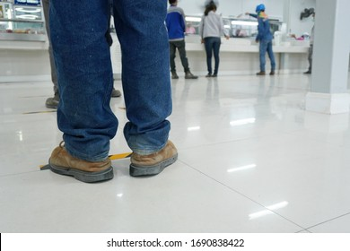 Worker stands before the yellow-black line up to wait to buy food in the factory canteen room during corona virus epidemic. (Covid 19)
