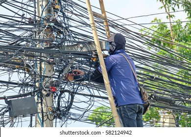 Worker stands on a bamboo ladder and works in unsafe condition with electrical wire.
