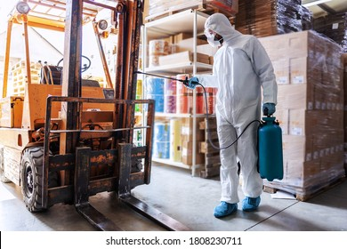 Worker in sterile uniform with rubber gloves holding sprayer with disinfectant and spraying forklift in warehouse. Corona outbreak concept.