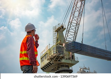 worker stevedore foreman, engineering, loading master talks to crane driver by walkie talkie for safety lifting the goods shipment, lifting by gantry crane, working at risk on the high level insurance