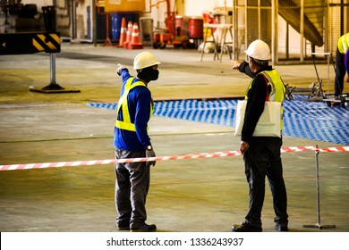 Worker stretching the red white warning tape to the pole at construction site.Red and white Hazardous restricted area tape at construction area of factory to mark territory works.
