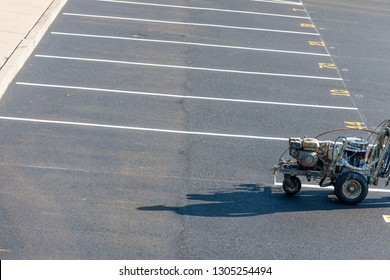 Worker with a striping mashing painting fresh lines in development parking lot, USA