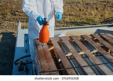 A worker in a suit, gloves, mask with equipment disinfects the surface in the warehouse. Sanitary treatment of the surface of a wooden box in the warehouse. Close-up.