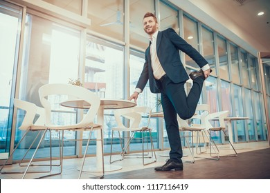 Worker in suit stretching leg at table in office. Stretching at Workplace.