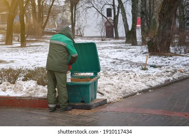 Worker takes sand and salt mixture from grit salt bin for spreading deicing chemicals on slippery sidewalk. Sprinkle salt on paving slabs to remove ice and prevent slipping accident