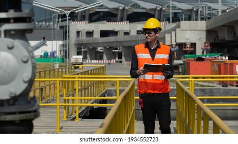 Worker taking note using pen and paper. male engineer checks equipment at work and records readings.