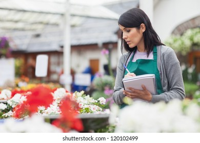 Worker taking notes while choosing a flower in the garden centre