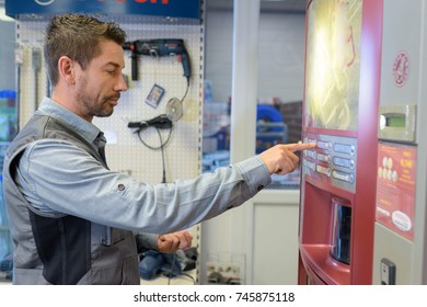 worker taking out drink from vending machine