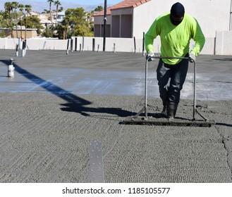 Worker Tamping Fresh Concrete Slab on Grade