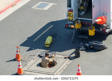 A worker in tan coveralls climbing up a ladder and out of a manhole equipment truck in view