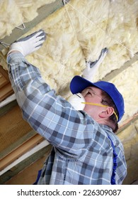 Worker thermally insulating a house attic using mineral wool