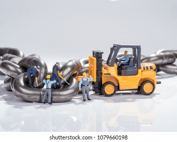 worker toys working on removing metal alloy steel chains for industrial use, very strong and hard for heavy load