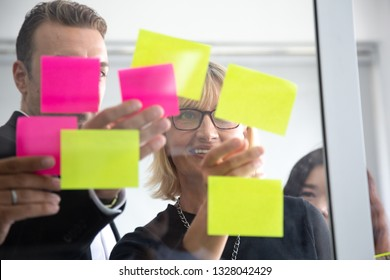 IT worker tracking his tasks on kanban board. Using task control of agile development methodology. Team members attaching sticky note to scrum task board in the office