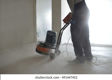 worker trowelling with power tool on concrete surface at new house construction site