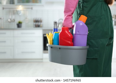Worker in uniform with basin of detergents in kitchen, closeup. Cleaning service