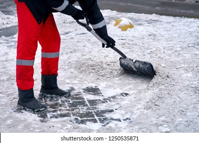 Worker in uniform cleaning snow with shovel in winter day. Man shoveling snow and ice after blizzard from sidewalk in the city. Janitor cleans driveway in snowstorm.