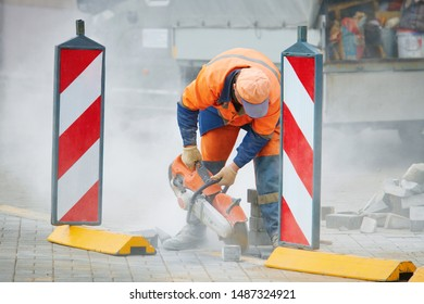 Worker in uniform cut concrete brick with circular saw. Repairing and renewal the walkway. Builder, work on laying paving slabs. Tiler cuts paving slab using petrol cut-off saw. Handheld rotary cutter