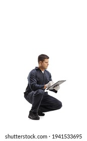 Worker in a uniform kneeling and writing a document isolated on white background