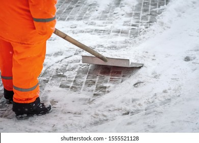 Worker in uniform shoveling snow on sidewalk after heavy snowfall. Municipal city service cleans footpath from snow after blizzard. Man shoveling path from snow. Janitor digging snow with shovel