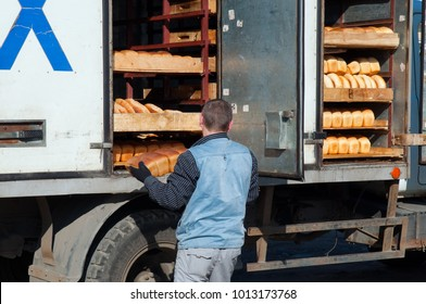 The worker unloads fresh bread from the truck