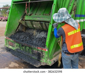 Worker of urban municipal loading waste water and garbage to the refuse truck.
