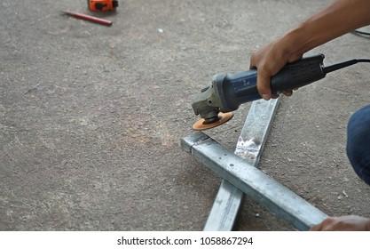 Worker used grinder metal an angle grinder on floor in workshop