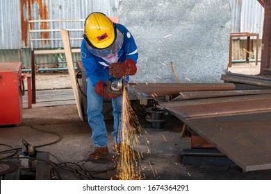 Worker is used Grinding Machine to grinding surface of H-Beam steel after cutting, at Industrial factory.