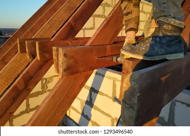 The worker uses a drill in the construction of the roof