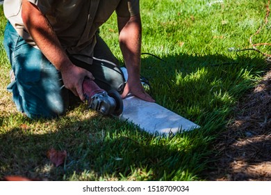 A worker uses a hand grinder tool to cut and shape a travertine tile in the grass on a patio construction job site.