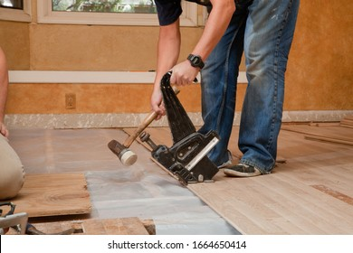 Worker uses Pneumatic Hardwood Nailer on a new floor installation.