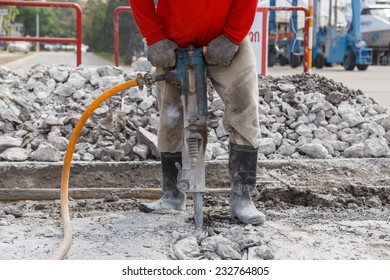 worker using construction drilling cement on the ground