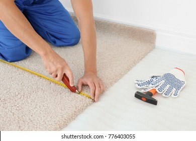 Worker using cutter while installing new carpet flooring in room