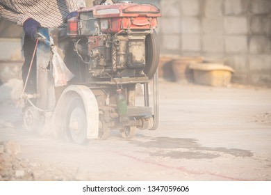 worker using cutting machine power tool to cut concrete floor with dirty dust spreading in air