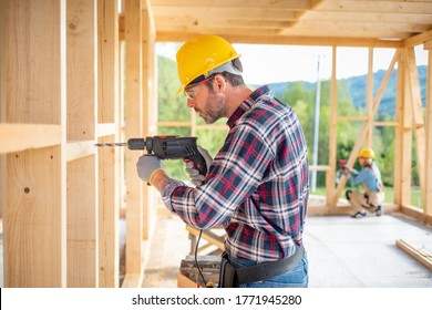 Worker using drill working on construction of wood frame house