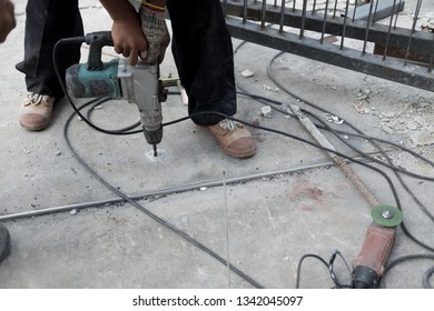 Worker using electric drill ground drilling by machine tool, construction workers.
