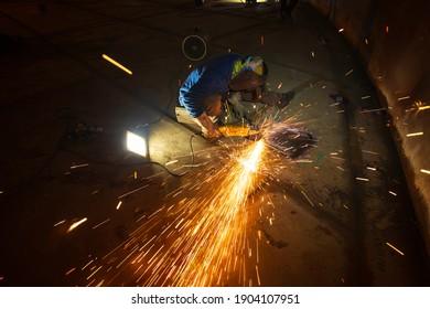 Worker using electric wheel spark grinding on welder metal carbon steel part bottom plate inside tank confined space
