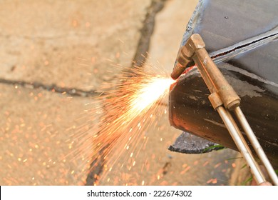 Worker using an Gas cutting torch to cut through metal in factory.