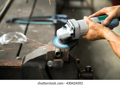 worker using grinder to do his work. A grinder have a sparkle flame.