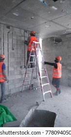 Worker using grinder on construction site for cutting cement block to electrical wiring.