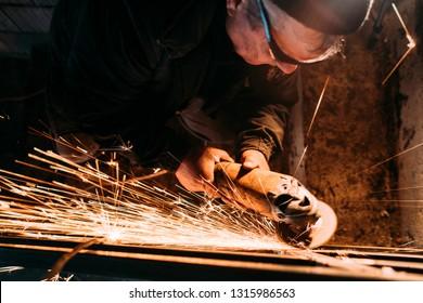 worker using grinder while working on steel metal railings