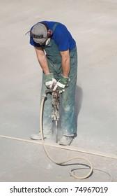 Worker using a handheld hydraulic hammer