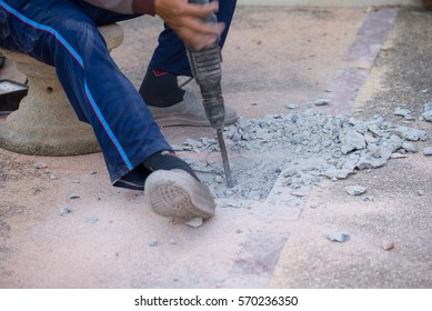 Worker using impact drill cement floor for repairing