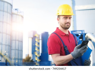 worker using mobile phone outside factory