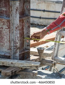 worker using a plumb bob for check pillar