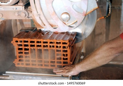 Worker is using power tool to make precise cut in red brick block. It uses abrasive action to slice through material as the saw rotates at high speed.