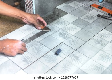 Worker using a ruler to measure and cut the pieces in installing ceramic floor tiles.