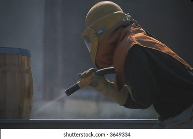 Worker using sandblasting equipment to clean up a wooden barrel